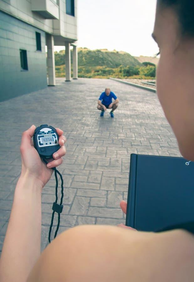 Χέρι εκπαιδευτών που χρησιμοποιεί το χρονόμετρο στο άτομο συγχρονισμού στοκ εικόνες