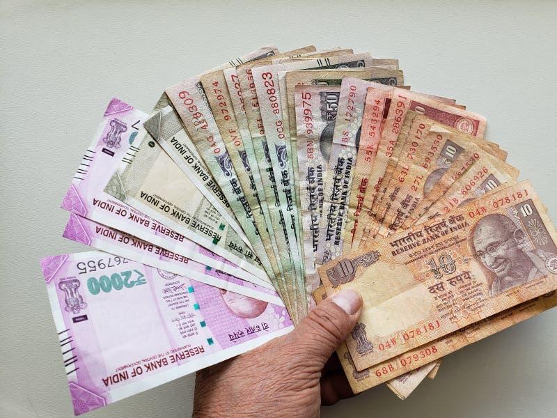 χέρι ενός ηληκιωμένου που κρατά τα ινδικά τραπεζογραμμάτια των διαφορετικών μετονομασιών στοκ φωτογραφίες με δικαίωμα ελεύθερης χρήσης