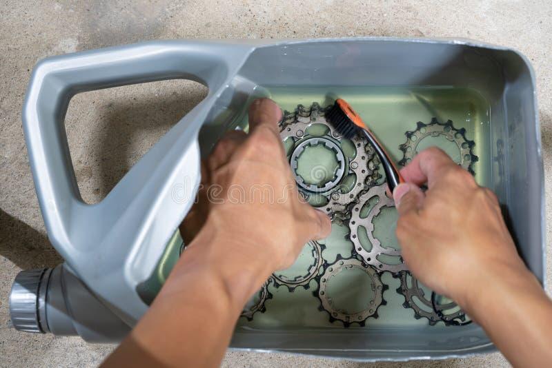 Χέρι ενός μηχανικού που καθαρίζει μια κασέτα ποδηλάτων από τα καύσιμα diesel στοκ φωτογραφία με δικαίωμα ελεύθερης χρήσης