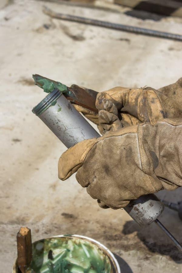 Χέρι ενός πυροβόλου όπλου λιπών πλήρωσης εργατών στοκ φωτογραφίες με δικαίωμα ελεύθερης χρήσης