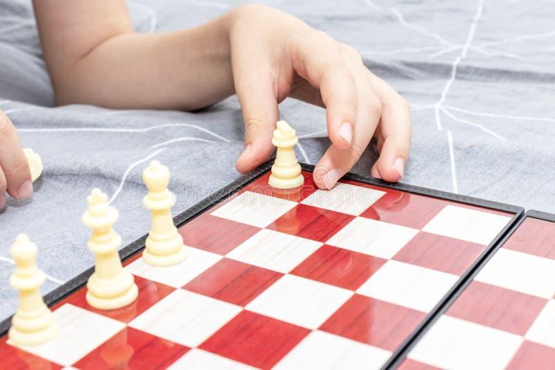 Χέρι ενός σκακιού παιχνιδιού παιδιών κοντά επάνω, των επιτραπέζιων παιχνιδιών και της έννοιας ψυχαγωγίας στοκ φωτογραφία