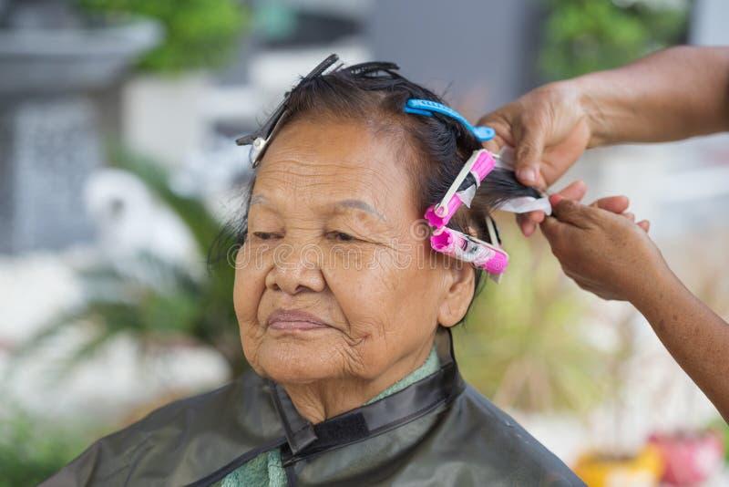 Χέρι ενός hairstylist που κάνει μια κυλώντας τρίχα perm της ανώτερης γυναίκας στοκ εικόνες