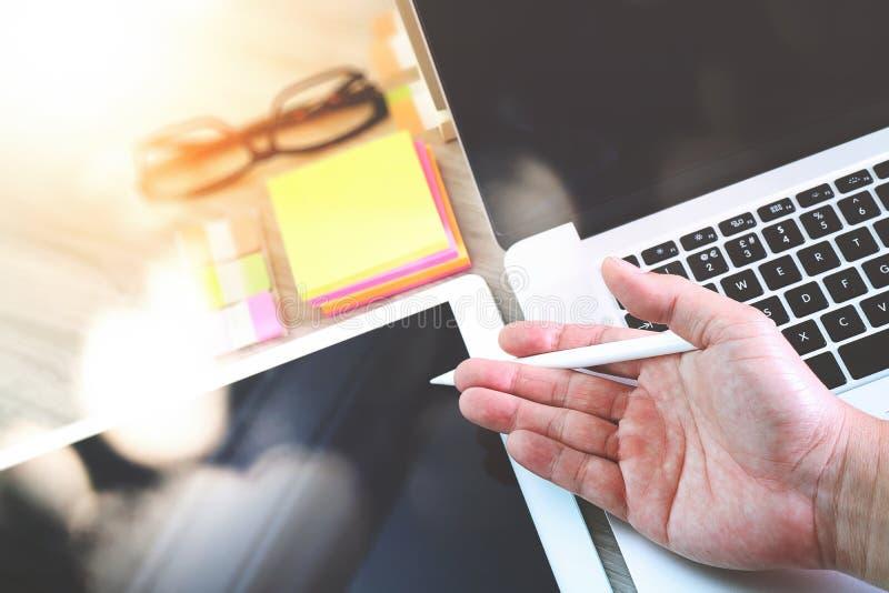 Χέρι επιχειρηματιών που λειτουργεί με τον ψηφιακούς υπολογιστή και το υπόμνημα ν ταμπλετών στοκ φωτογραφίες