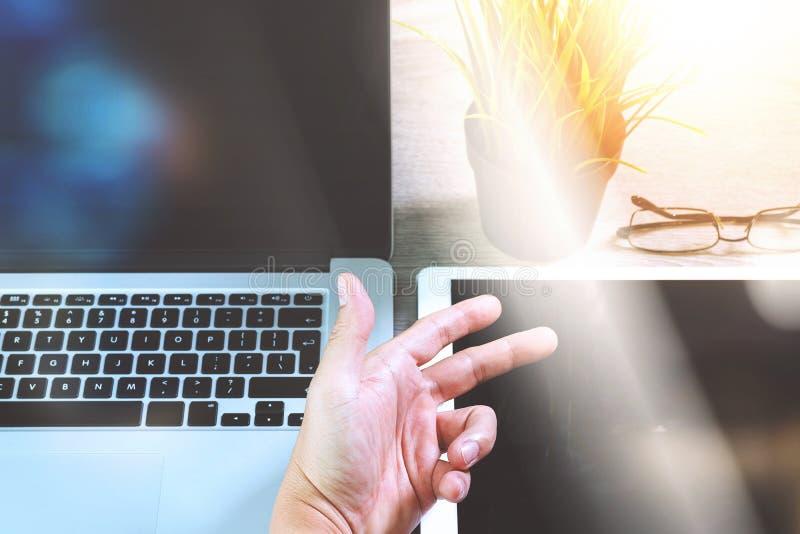 Χέρι επιχειρηματιών που λειτουργεί με τον ψηφιακούς υπολογιστή και το υπόμνημα ν ταμπλετών στοκ εικόνα