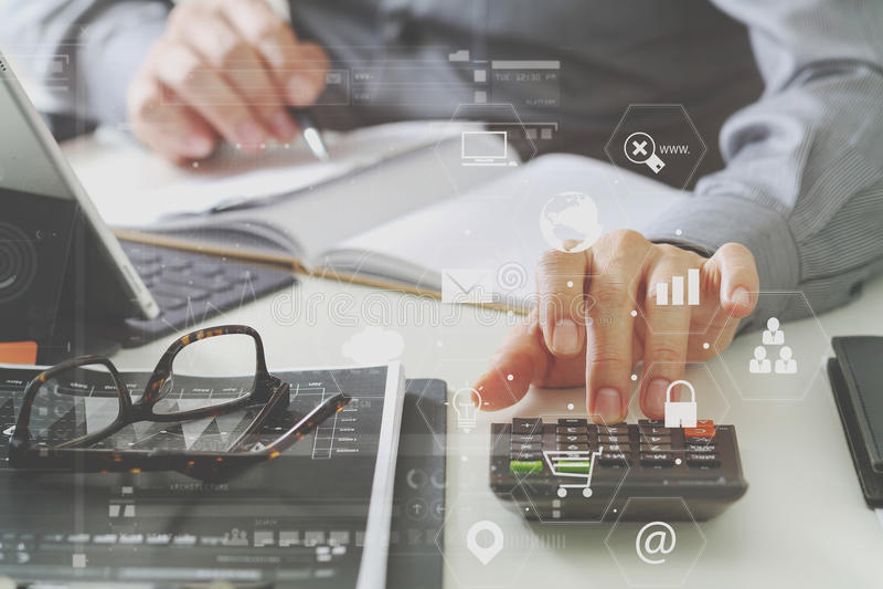 χέρι επιχειρηματιών που λειτουργεί με τους πόρους χρηματοδότησης για το κόστος και τον υπολογιστή απεικόνιση αποθεμάτων