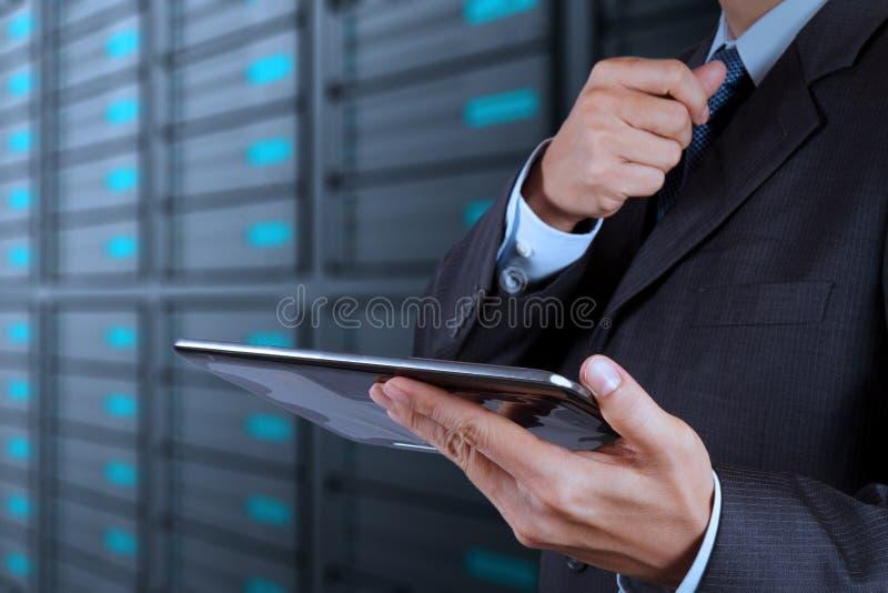 Χέρι επιχειρηματιών που χρησιμοποιεί τον υπολογιστή ταμπλετών και το δωμάτιο κεντρικών υπολογιστών στοκ φωτογραφία