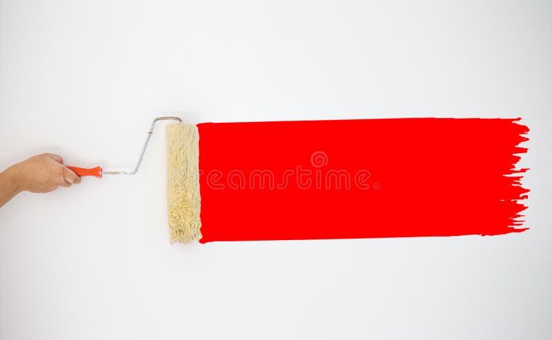 Χέρι ζωγράφων ` s - κρατημένος κύλινδρος στη ζωγραφική των χρωμάτων κόκκινου χρώματος στον γκρίζο τοίχο στοκ φωτογραφία με δικαίωμα ελεύθερης χρήσης