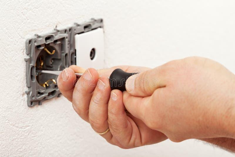 Χέρι ηλεκτρολόγων που τοποθετεί ένα προσάρτημα τοίχων στοκ εικόνα