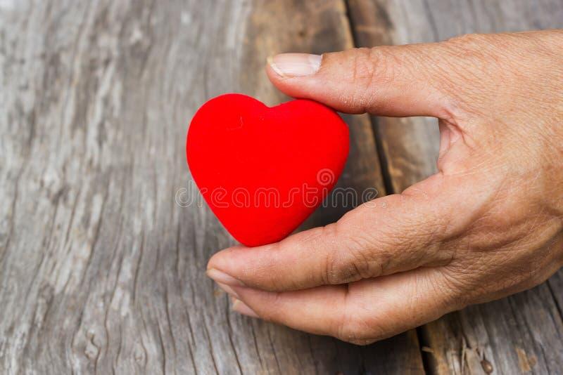 Χέρι ηλικιωμένης γυναίκας που κρατά μια κόκκινη μορφή καρδιών στοκ φωτογραφία με δικαίωμα ελεύθερης χρήσης