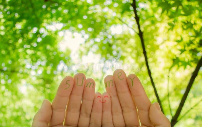 Χέρι και θερινή λέξη στο πράσινο υπόβαθρο φύλλων στοκ εικόνα με δικαίωμα ελεύθερης χρήσης