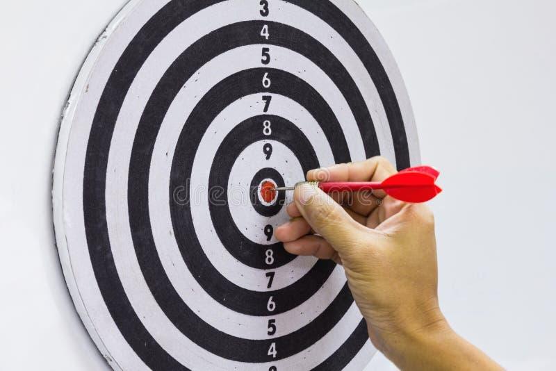 Χέρι και κόκκινο βέλος στο dartboard στοκ φωτογραφίες με δικαίωμα ελεύθερης χρήσης
