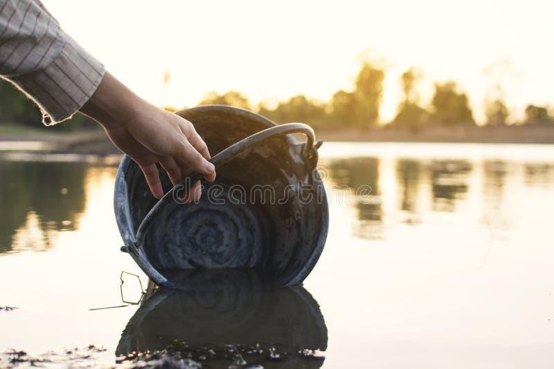 Χέρι κινηματογραφήσεων σε πρώτο πλάνο της γυναίκας που κρατά έναν κάδο στη λίμνη στοκ εικόνες