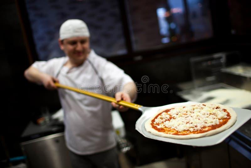 Χέρι κινηματογραφήσεων σε πρώτο πλάνο του αρτοποιού αρχιμαγείρων στην άσπρη ομοιόμορφη πίτσα παραγωγής στην κουζίνα στοκ φωτογραφία