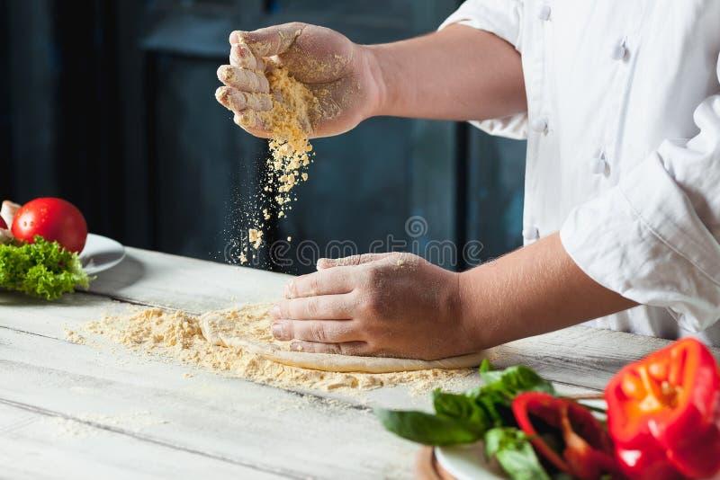 Χέρι κινηματογραφήσεων σε πρώτο πλάνο του αρτοποιού αρχιμαγείρων στην άσπρη ομοιόμορφη πίτσα παραγωγής στην κουζίνα στοκ εικόνες
