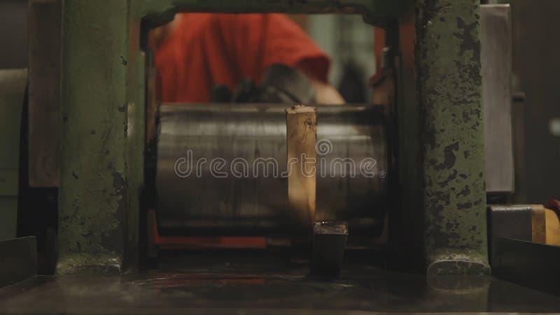 Χέρι-κυλημένοι χρυσοί φραγμοί Ρόλος επεξεργασίας βιομηχανικών εργατών του φύλλου χάλυβα Βιομηχανία μετάλλων Μηχανή κυλώντας μύλων στοκ φωτογραφίες