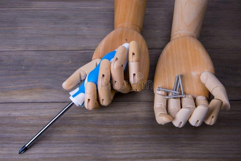 Χέρι με ένα κατσαβίδι και μερικές βίδες στοκ εικόνες