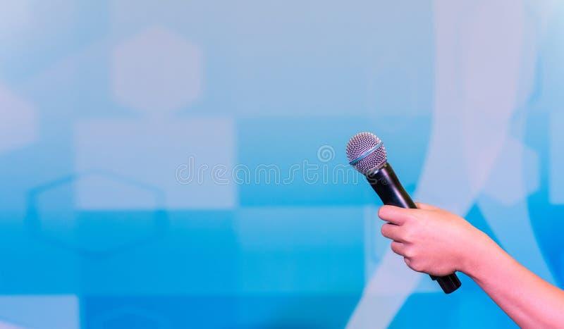 Χέρι με ένα μικρόφωνο στο υπόβαθρο Κινηματογράφηση σε πρώτο πλάνο ενός μικροφώνου εκμετάλλευσης χεριών προσώπων ` s στοκ φωτογραφίες