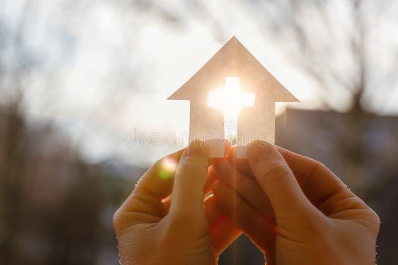 Χέρι με ένα σπίτι από το έγγραφο και έναν σταυρό στοκ φωτογραφία
