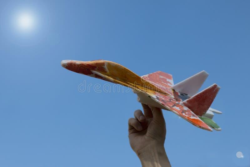 Χέρι με ένα σπιτικό αεροσκάφος σε ένα υπόβαθρο του καθαρού μπλε ουρανού στοκ εικόνα