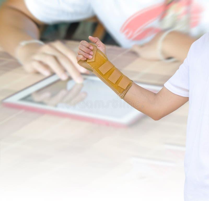 Χέρι με ένα στήριγμα καρπών στη θολωμένη χρησιμοποίηση χεριών υποβάθρου σύγχρονη στοκ εικόνες