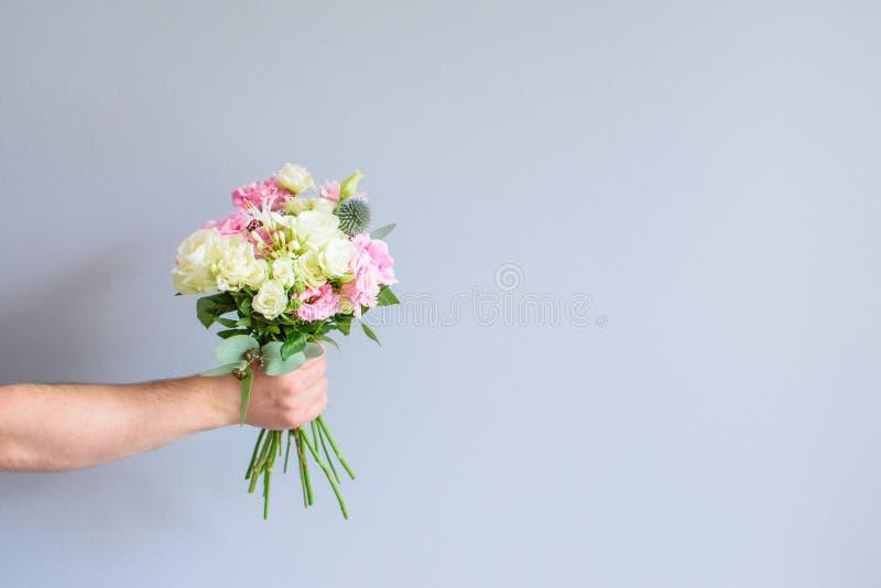 Χέρι με μια ανθοδέσμη των λουλουδιών στοκ φωτογραφία με δικαίωμα ελεύθερης χρήσης