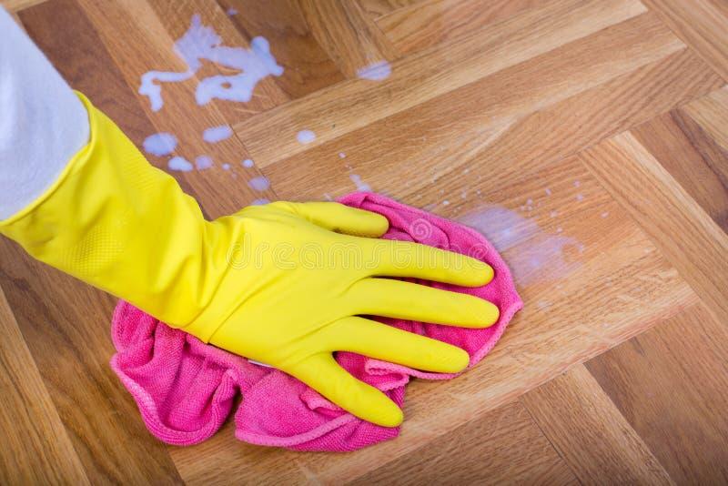 Χέρι με τα γάντια που σκουπίζουν το πάτωμα στοκ φωτογραφία