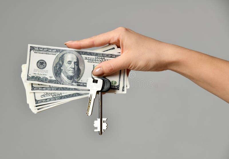 Χέρι με τα χρήματα και με τα κλειδιά από το σπίτι τα επίπεδα κτημάτων στεγάζουν την πραγματική πώληση μισθώματος στοκ εικόνες