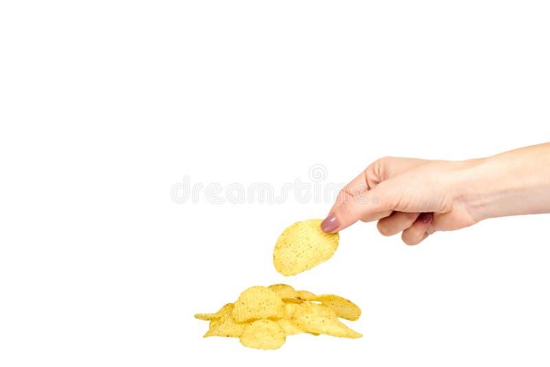 Χέρι με τα χρυσά τσιπ πατατών χρώματος, τραγανός και κυματιστός στοκ φωτογραφίες