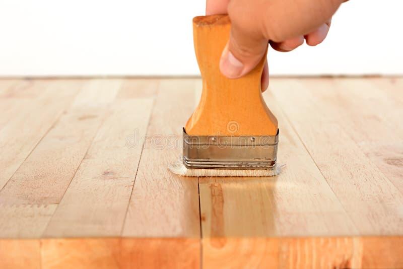 Χέρι με τη βούρτσα που ισχύει στον ξύλινο πίνακα στοκ εικόνες