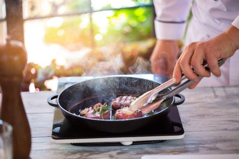 Χέρι με το κρέας αφών λαβίδων στοκ εικόνες