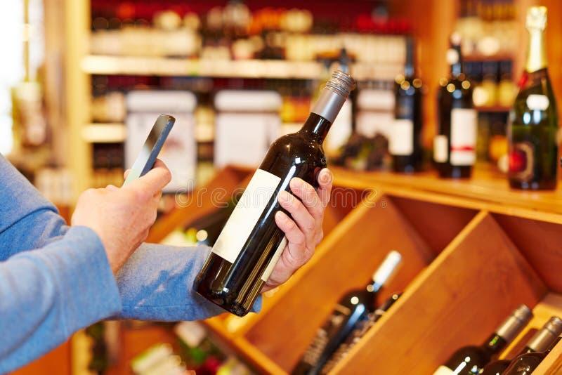 Χέρι με το μπουκάλι κρασιού ανίχνευσης smartphone στοκ φωτογραφία