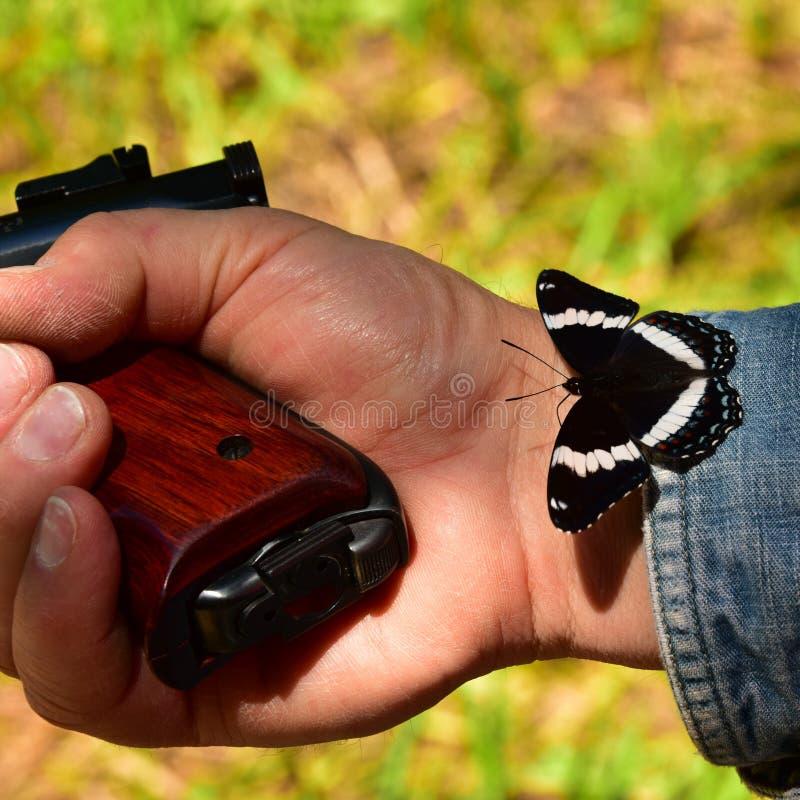 Χέρι με το πυροβόλο όπλο και την πεταλούδα στοκ εικόνες