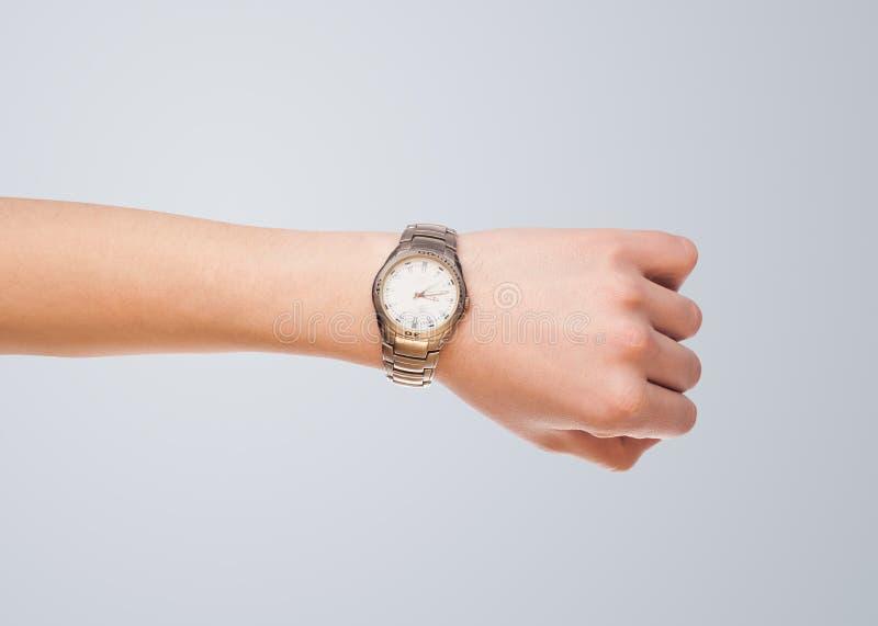 Χέρι με το ρολόι που παρουσιάζει ακριβή χρόνο στοκ εικόνα με δικαίωμα ελεύθερης χρήσης