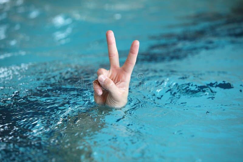 Χέρι με δύο δάχτυλα επάνω στο σύμβολο νίκης ή ειρήνης, ανωτέρω - νερό στοκ φωτογραφία με δικαίωμα ελεύθερης χρήσης