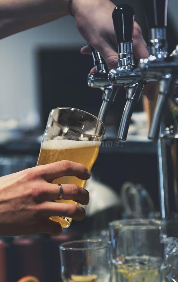Χέρι μπάρμαν στη βρύση μπύρας που ρίχνει μια μπύρα σε ποτήρι στοκ φωτογραφία