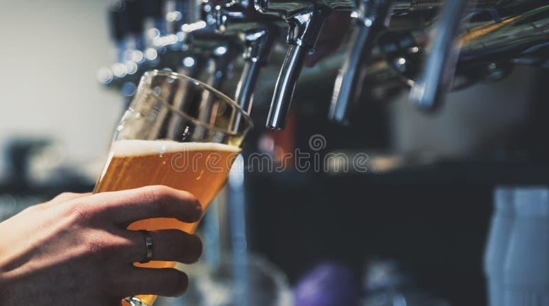 Χέρι μπάρμαν στη βρύση μπύρας που ρίχνει μια μπύρα σε ποτήρι στοκ φωτογραφίες με δικαίωμα ελεύθερης χρήσης
