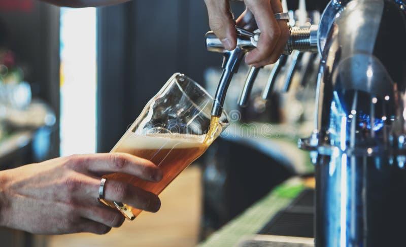 Χέρι μπάρμαν στη βρύση μπύρας που ρίχνει μια μπύρα σε ποτήρι στοκ εικόνα με δικαίωμα ελεύθερης χρήσης
