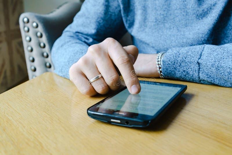Χέρι νεαρών άνδρων σχετικά με ένα smartphone στον καφέ κατά τη διάρκεια του καφές-σπασίματος στοκ εικόνες με δικαίωμα ελεύθερης χρήσης