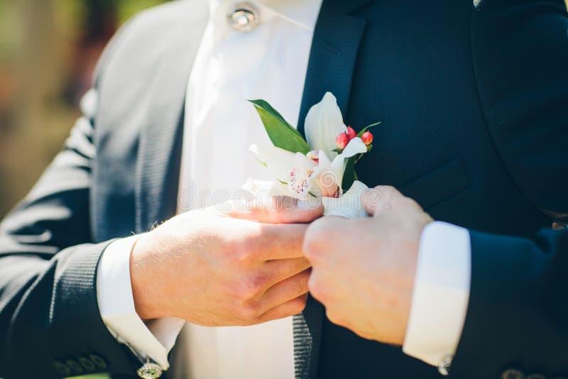 Χέρι νεόνυμφου που τακτοποιεί το λουλούδι μπουτονιέρων στοκ εικόνα με δικαίωμα ελεύθερης χρήσης