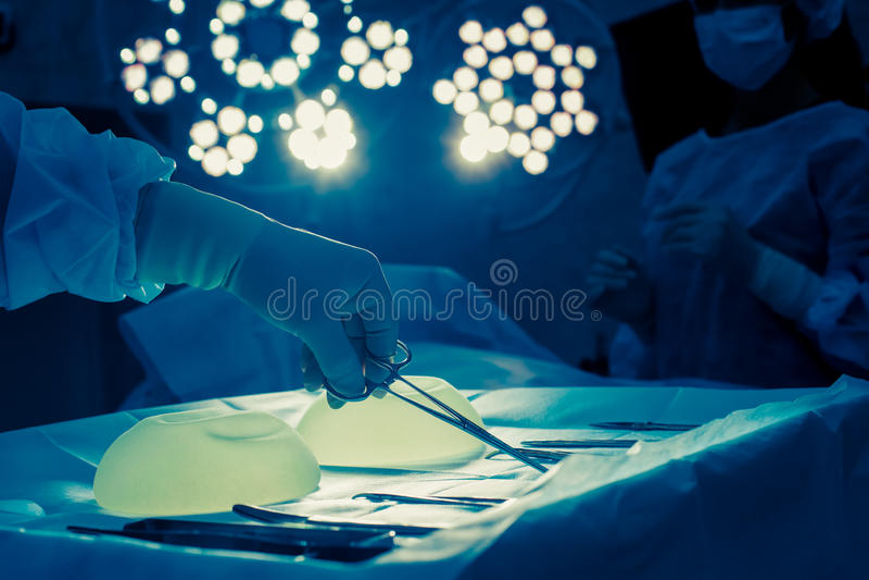 Χέρι νοσοκόμων που παίρνει το χειρουργικό όργανο για την ομάδα χειρούργων στο β στοκ εικόνα με δικαίωμα ελεύθερης χρήσης