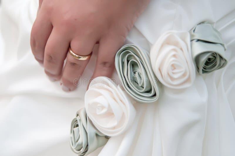 Χέρι νύφης που φορά το γαμήλιο δαχτυλίδι στοκ εικόνες