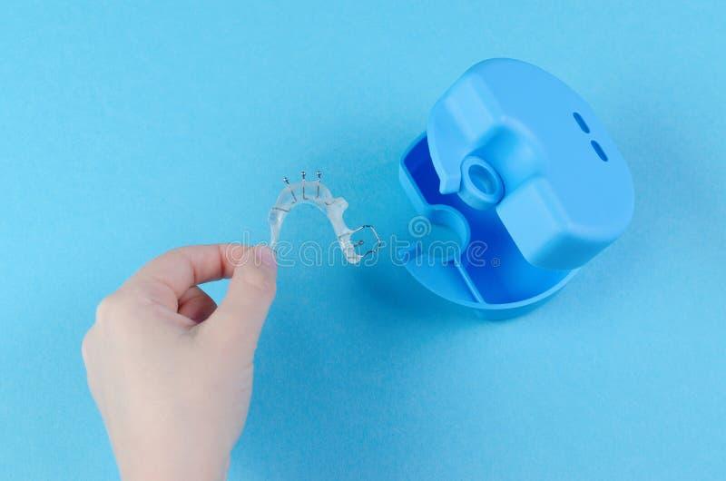 Χέρι παιδιού με τη orthodontic συσκευή με το κιβώτιο στο μπλε υπόβαθρο στοκ φωτογραφία με δικαίωμα ελεύθερης χρήσης