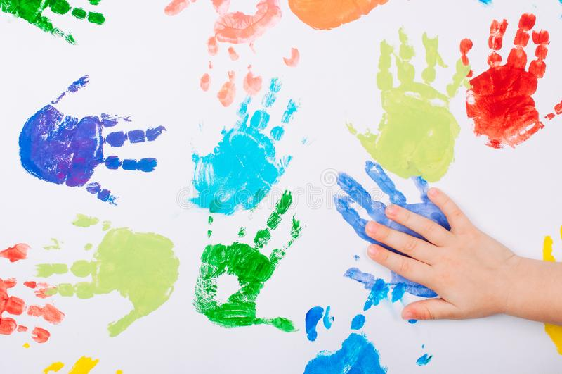 Χέρι παιδιών που κάνει χρωματισμένο handprints στο άσπρο υπόβαθρο στοκ εικόνα