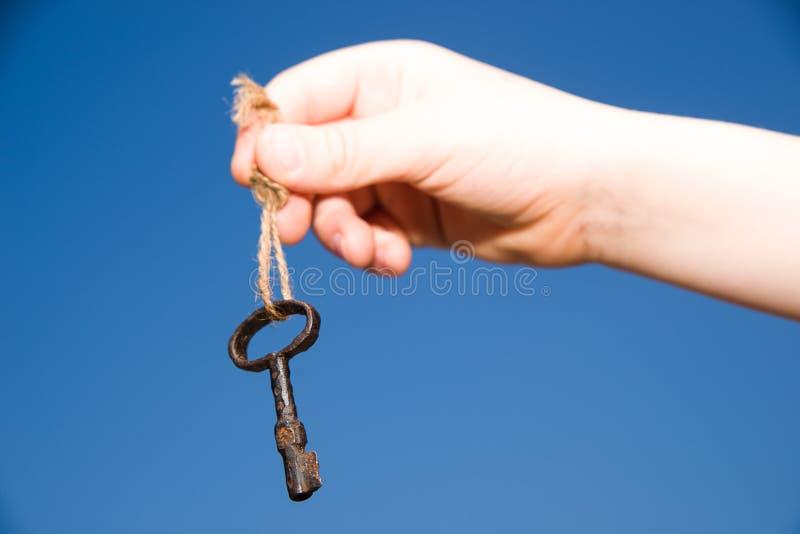 Χέρι παιδιών που κρατά ένα παλαιό κλειδί σε μια σειρά στοκ φωτογραφία