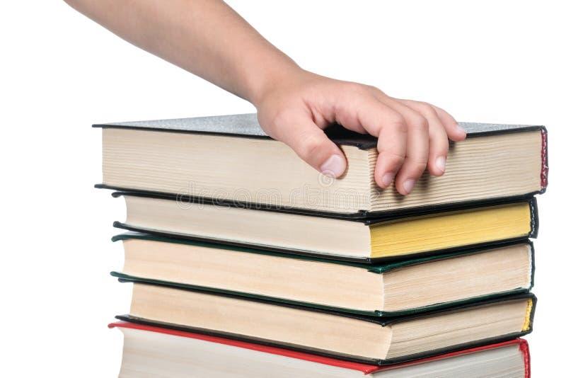 Χέρι παιδιών σε έναν σωρό των βιβλίων στοκ φωτογραφία με δικαίωμα ελεύθερης χρήσης