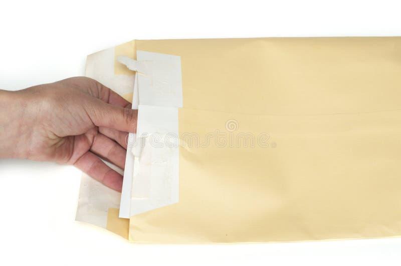 Χέρι που ανοίγει μια επιστολή από τον καφετή φάκελο στοκ φωτογραφία με δικαίωμα ελεύθερης χρήσης