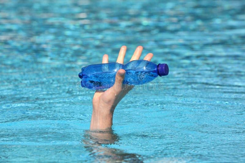 Χέρι που αυξάνει από την εκμετάλλευση νερού το πλαστικό μπλε μπουκάλι νερό στοκ εικόνα με δικαίωμα ελεύθερης χρήσης