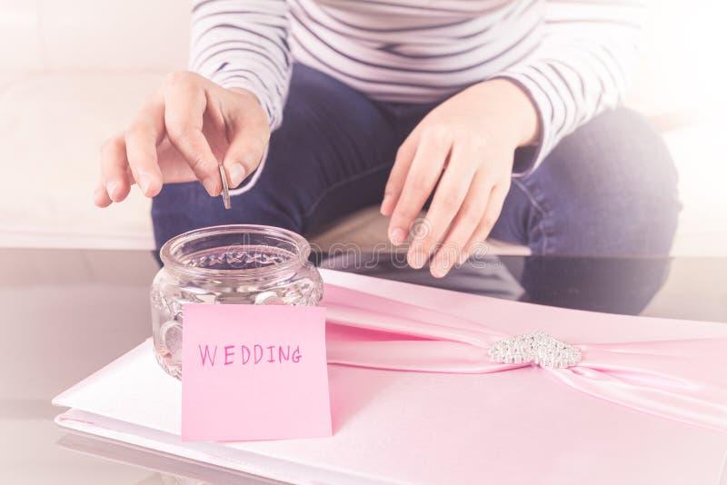 Χέρι που βάζει ένα νόμισμα στα βάζα γυαλιού με το «γαμήλιο» κείμενο στοκ εικόνες