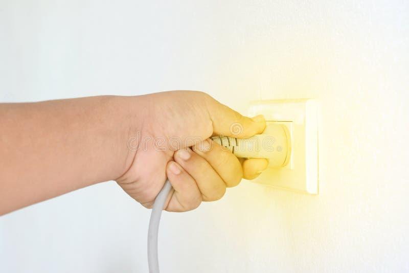 Χέρι που βάζει το ηλεκτρικό βούλωμα στην υποδοχή στοκ φωτογραφία