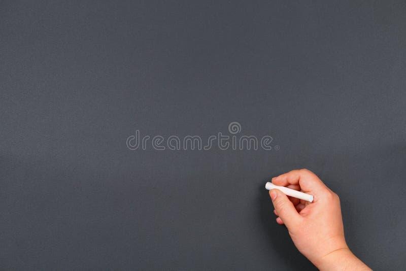 Χέρι που γράφει από την άσπρη κιμωλία σε έναν πίνακα Χρήσιμος ως διάστημα υποβάθρου για το κείμενο ή την εικόνα στοκ εικόνες